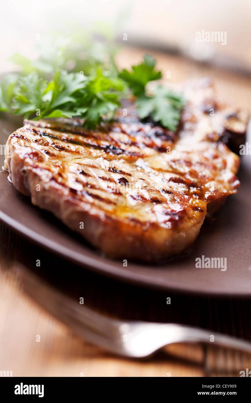 saftig gegrilltes Schweinekotelett (Hals geschnitten) mit grünen Stockbild