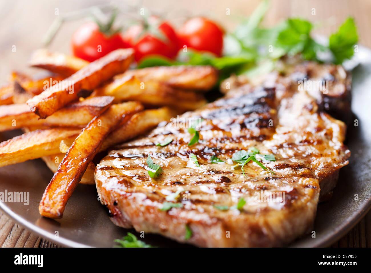 Steak und Pommes mit Salat Stockbild