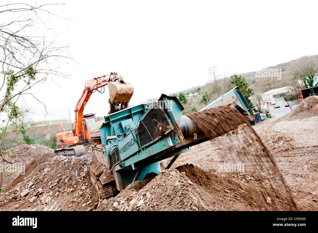 Digger laden Schutt auf recycling-Förderband Stockbild