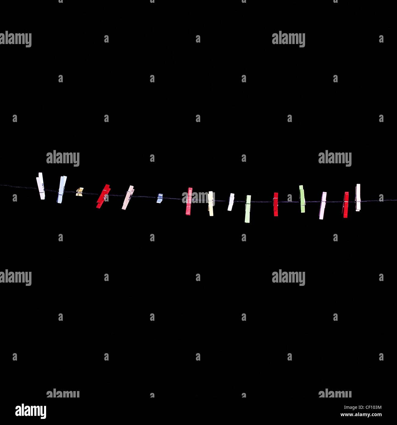 mehr bunten Wäscheklammern in einer Zeile auf einem schwarzen Hintergrund Stockbild
