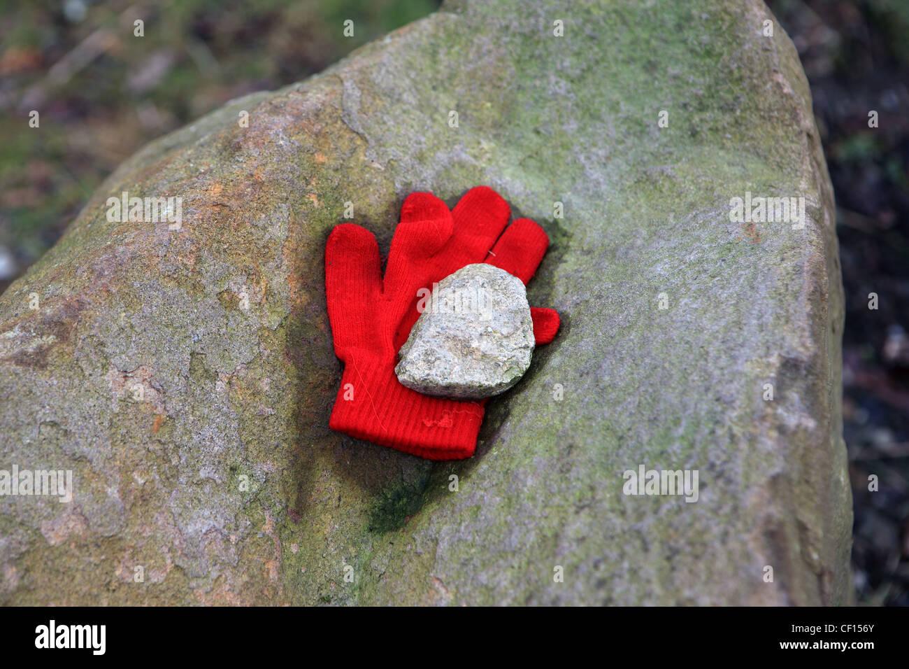 Rot wollenen Handschuh verloren mit Stein festhalten großer Felsen Stockbild