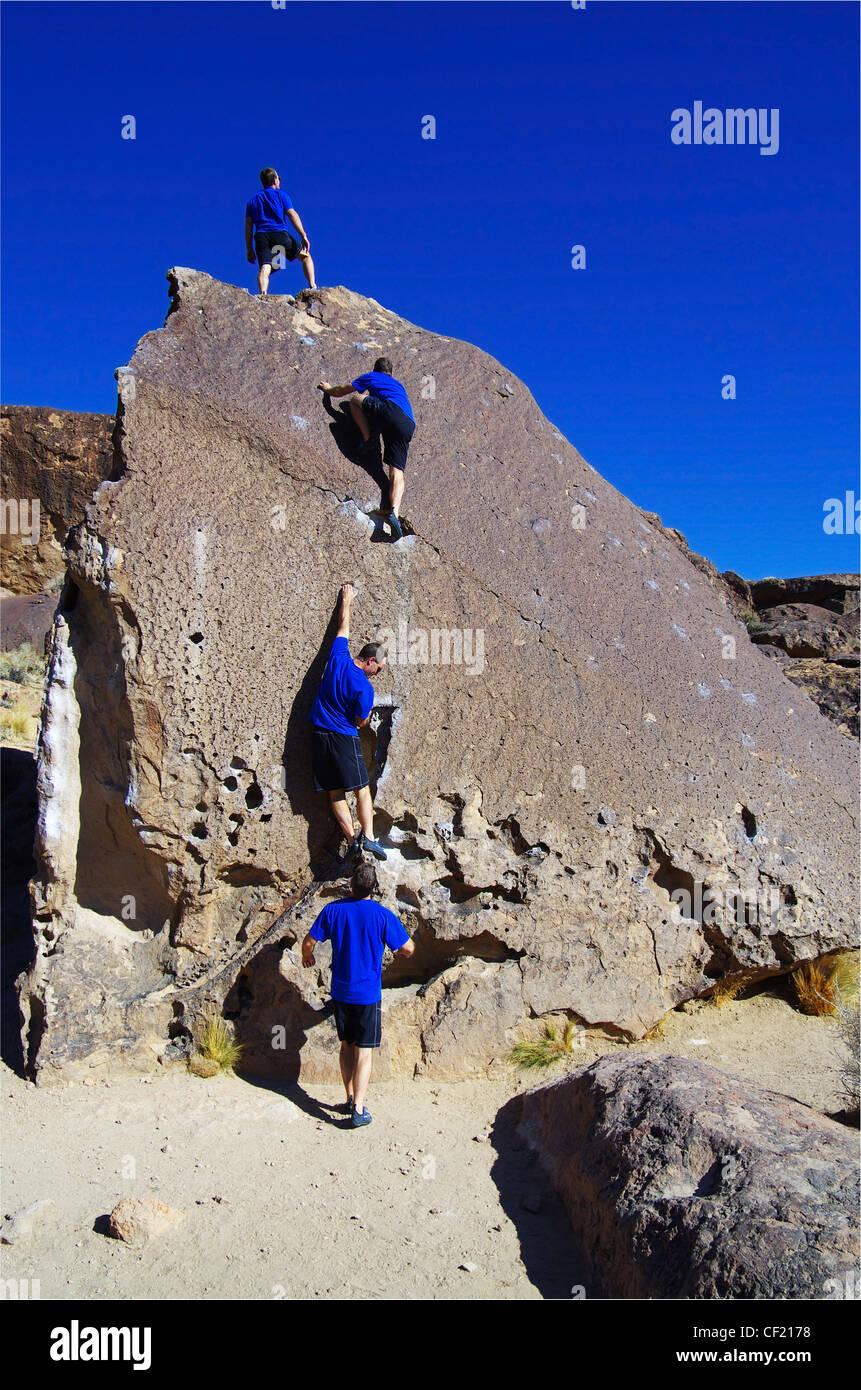 eine zusammengesetzte Reihe von ein Mann Klettern auf einem Felsblock Stockfoto