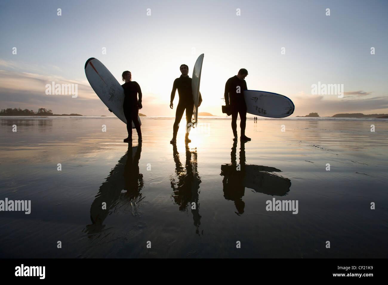Silhouette der drei Surfer Surfboards tragen; Chesterman Beach Tofino Vancouver Island in British Columbia Kanada Stockbild