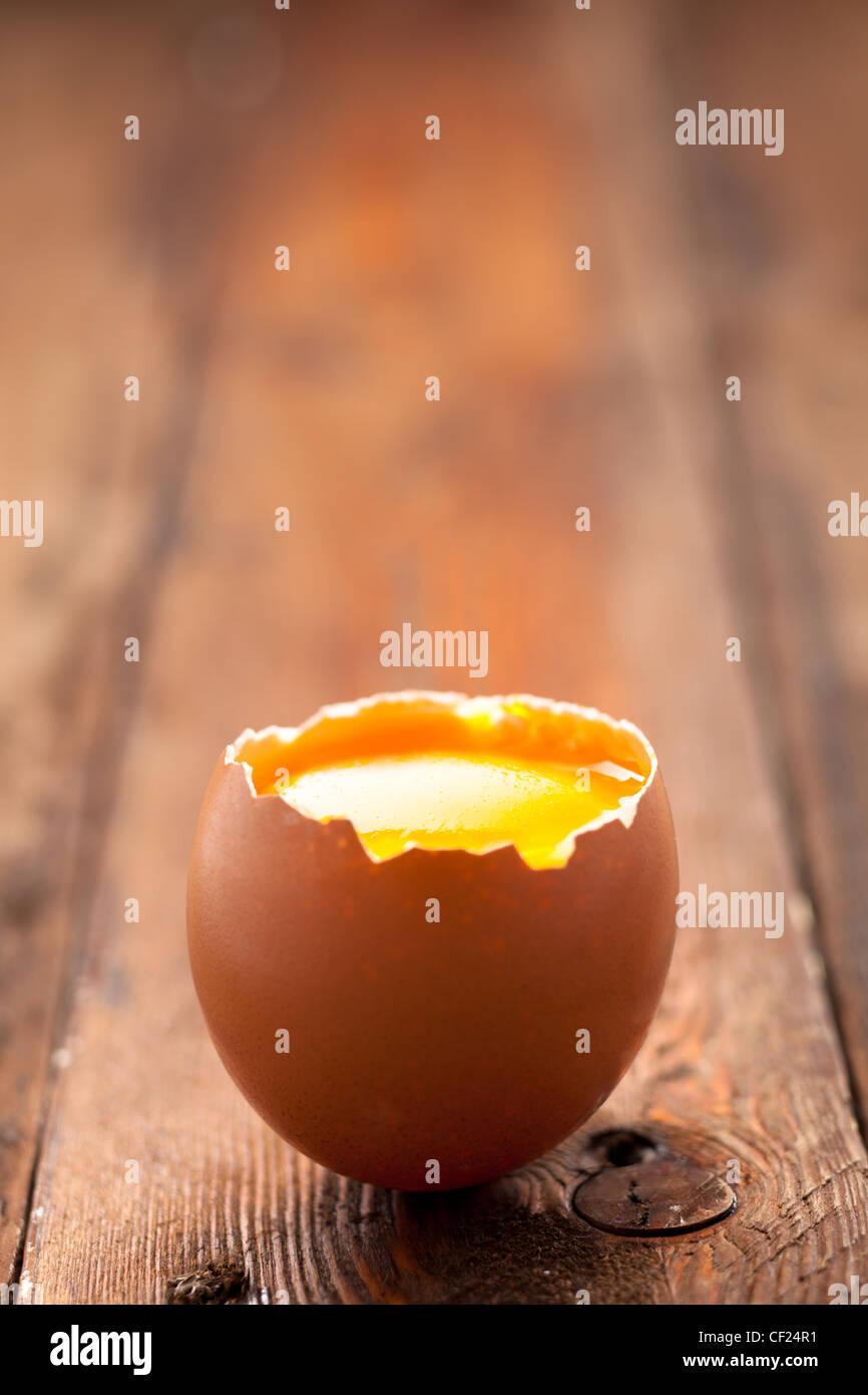 Eierschale mit Eigelb auf Holz eröffnet Stockbild