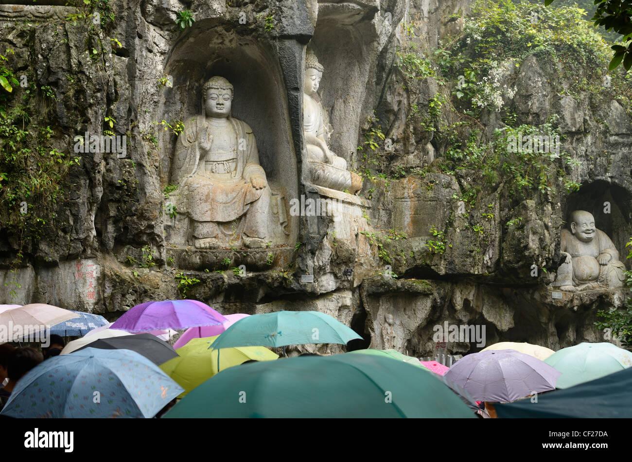 Kalkstein Buddha Skulpturen in feilai Feng im Regen mit Sonnenschirmen ling Yin Tempel Hangzhou China Stockbild