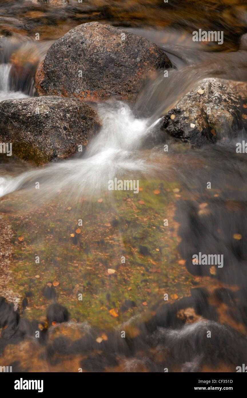 Eine Nahaufnahme des Wassers, das über Felsen in ein Brennen im Norden Glen Sannox auf der Isle of Arran. Stockbild