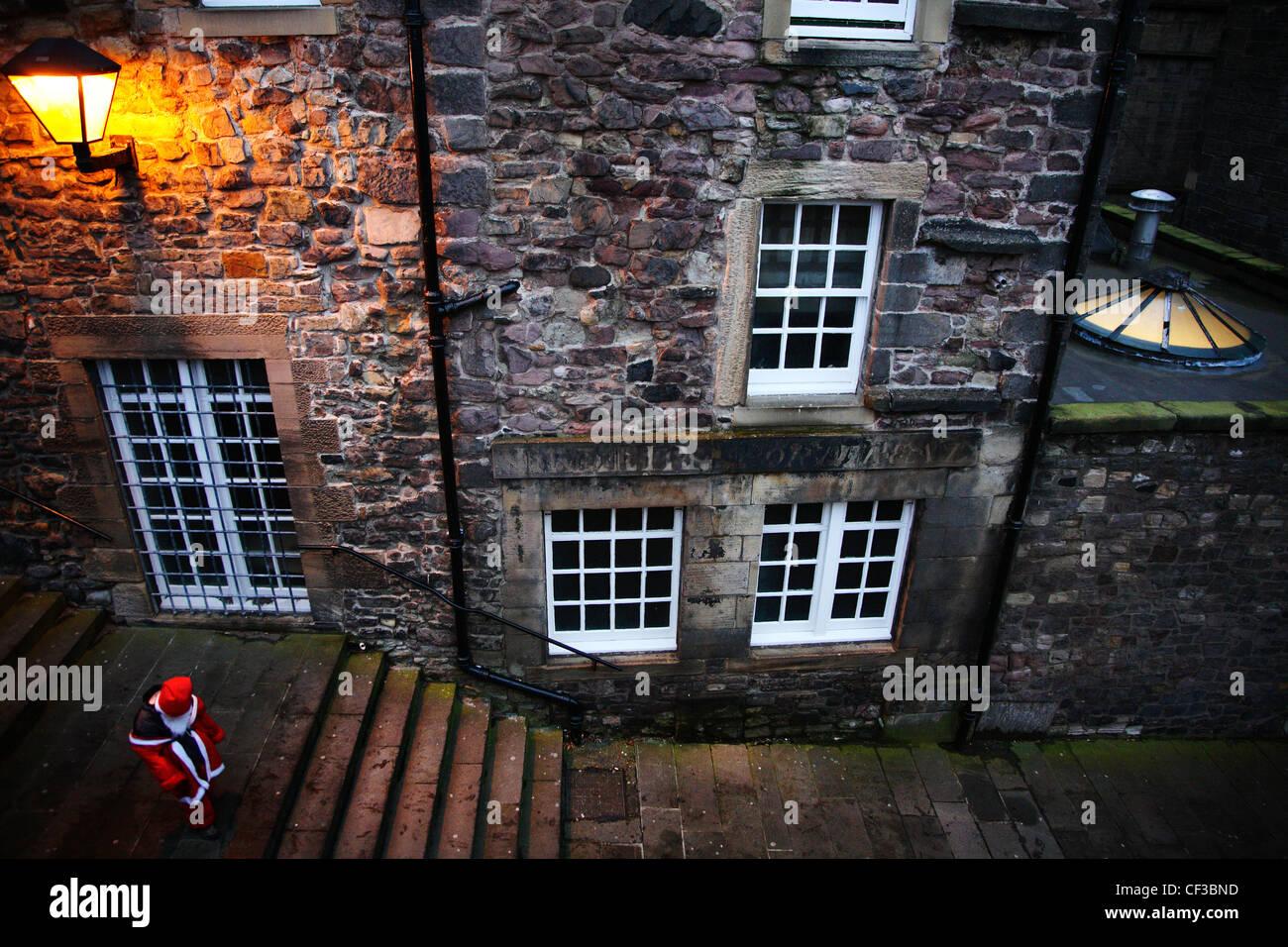 Blick hinunter auf der Straße zu einer Person in Tracht während der Edinburgh Weihnachten Santa schlendern. Stockbild