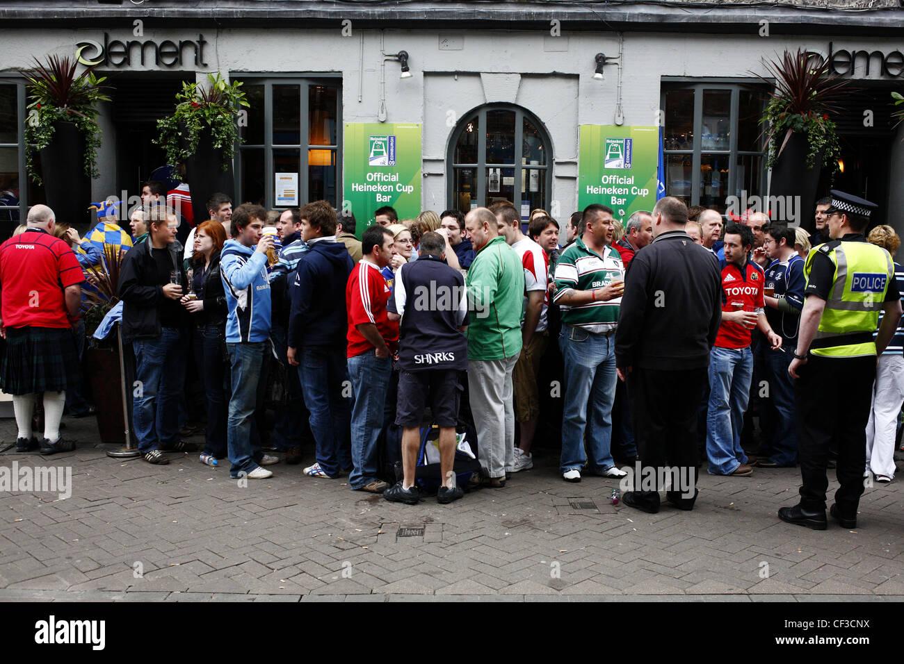 Ein Security-Agent und Polizisten haben ein wachsames Auge auf Rugby-Fans vor einer Bar. Stockbild