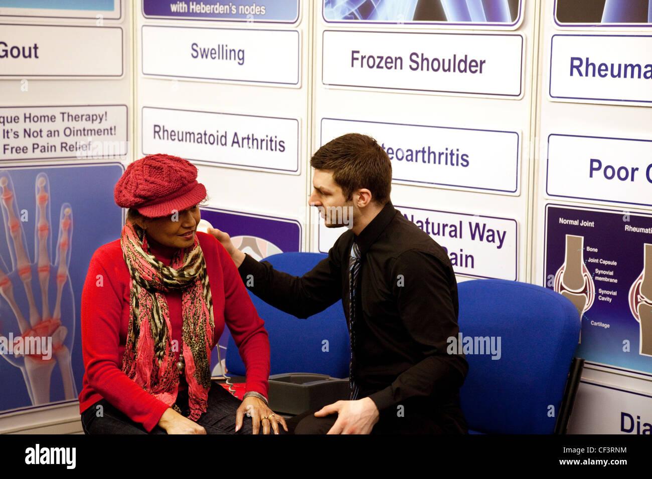 Eine Patientin, die Rücksprache mit einem männlichen Arzt über Arthritis der Schulter, dem Rücken Stockbild
