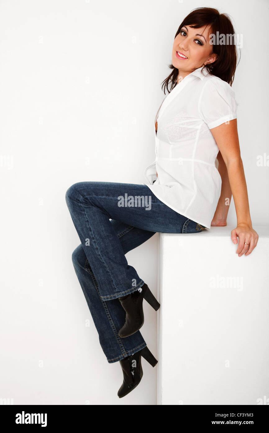 d69cf12cc29f Porträt von Mädchen in Jeans und weißem Hemd im weißen Studio sitzen.  Hochformat.
