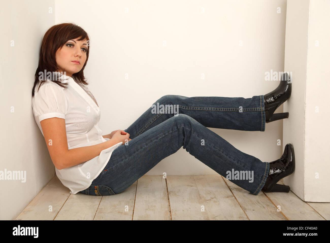 911cc32995c8 Porträt von nachdenklich Mädchen in Jeans und weißem Hemd im weißen Studio  sitzen.