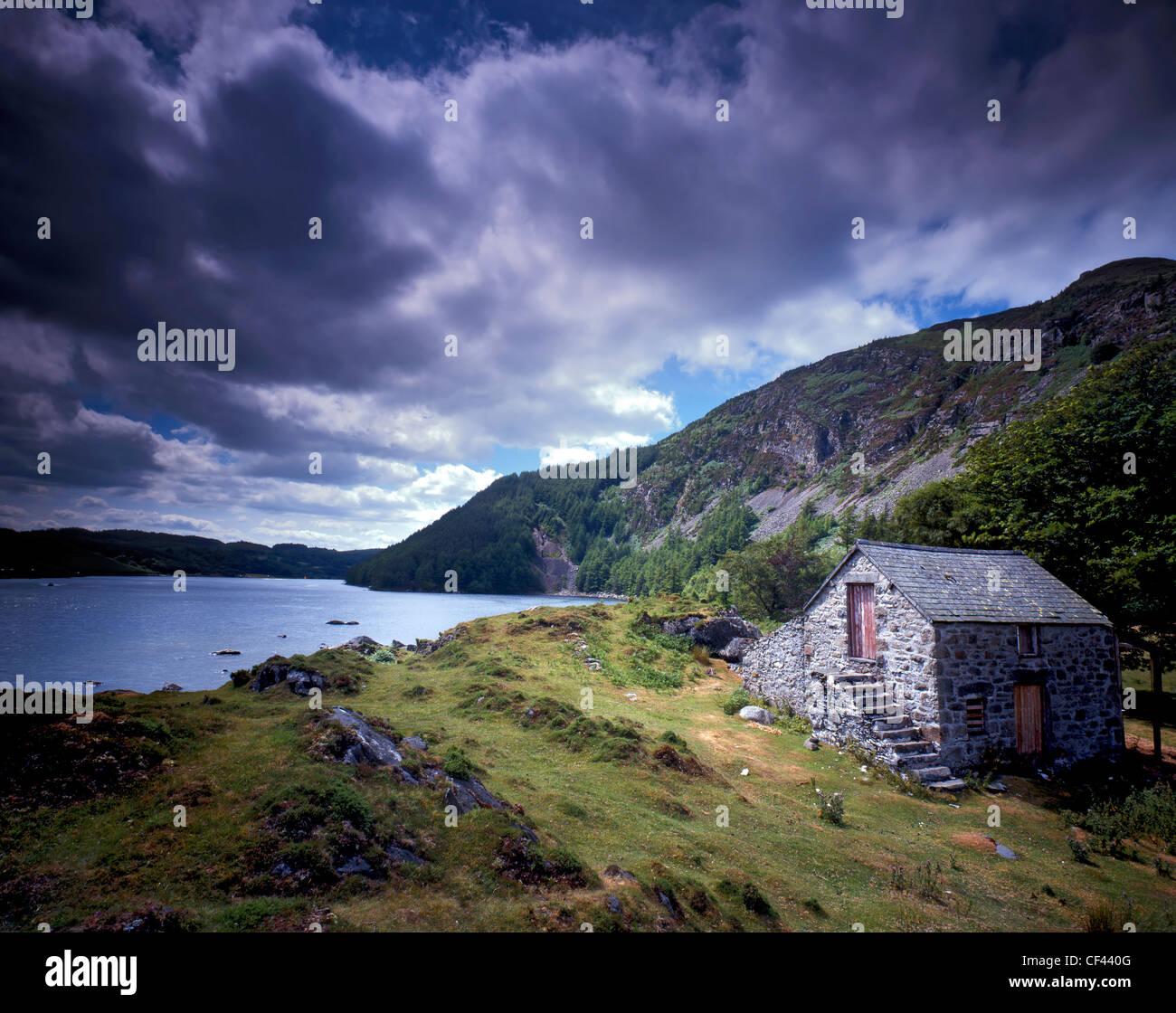 Blick über Llyn Geirionydd, einen abgelegenen See in Snowdonia wie Gewitterwolken über Kopf sammeln. Stockbild
