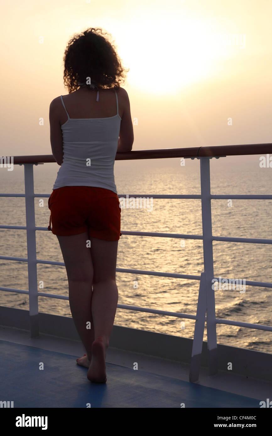 Mädchen stand am Schiffsdeck und sah in der Ferne Blick von zurück Ganzkörper Stockbild