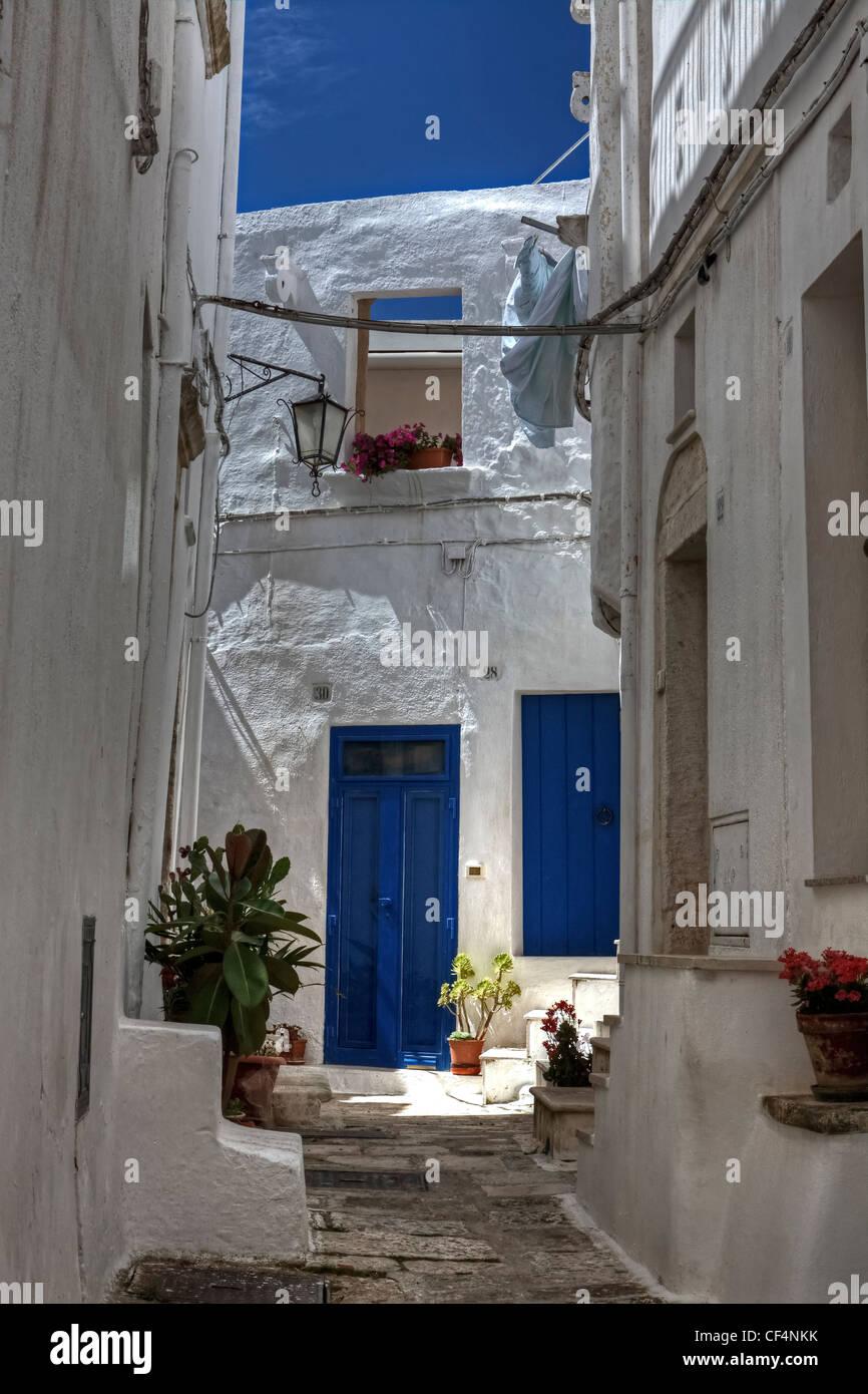 Hinterhof mit blauen Türen und weiße Wände in Apulien, Italien Stockbild