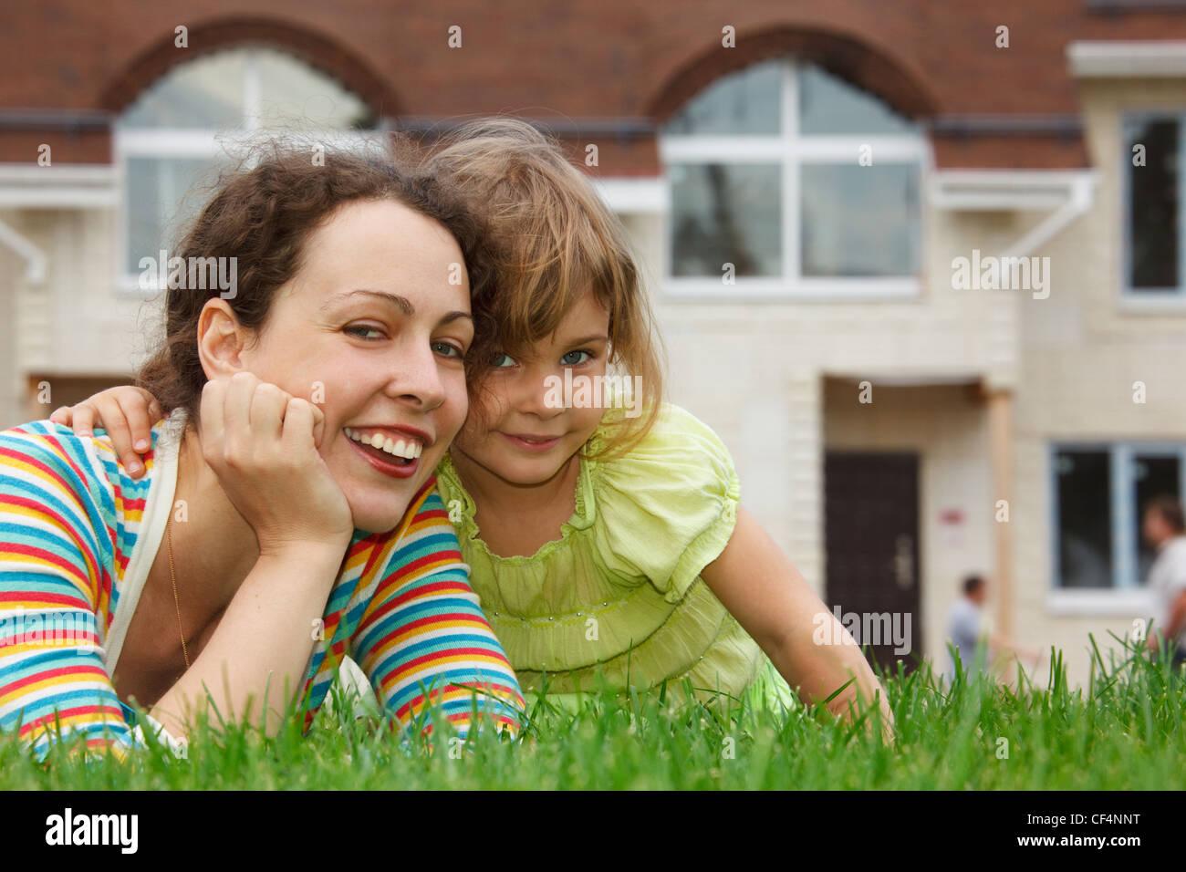 Mutter und Tochter auf Rasen vor neues Zuhause liegen. Sie Lächeln und schauen in die Kamera. Stockbild