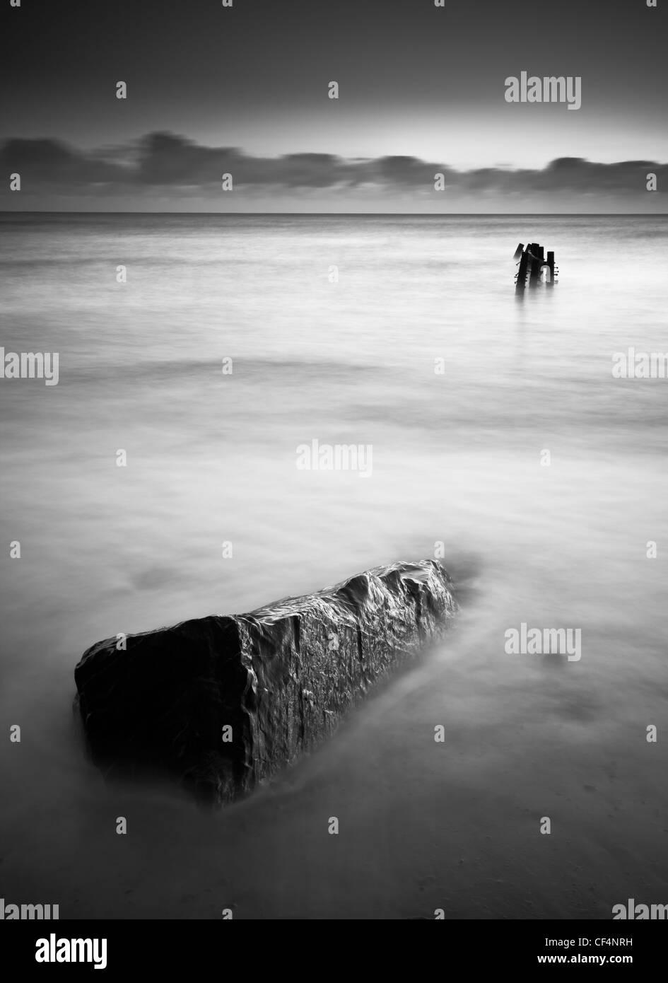 Ein einzelner Felsen in das Meer zeigt in die Richtung von einem verlorenen Steg auf der Nord-Ost Küste von Stockbild
