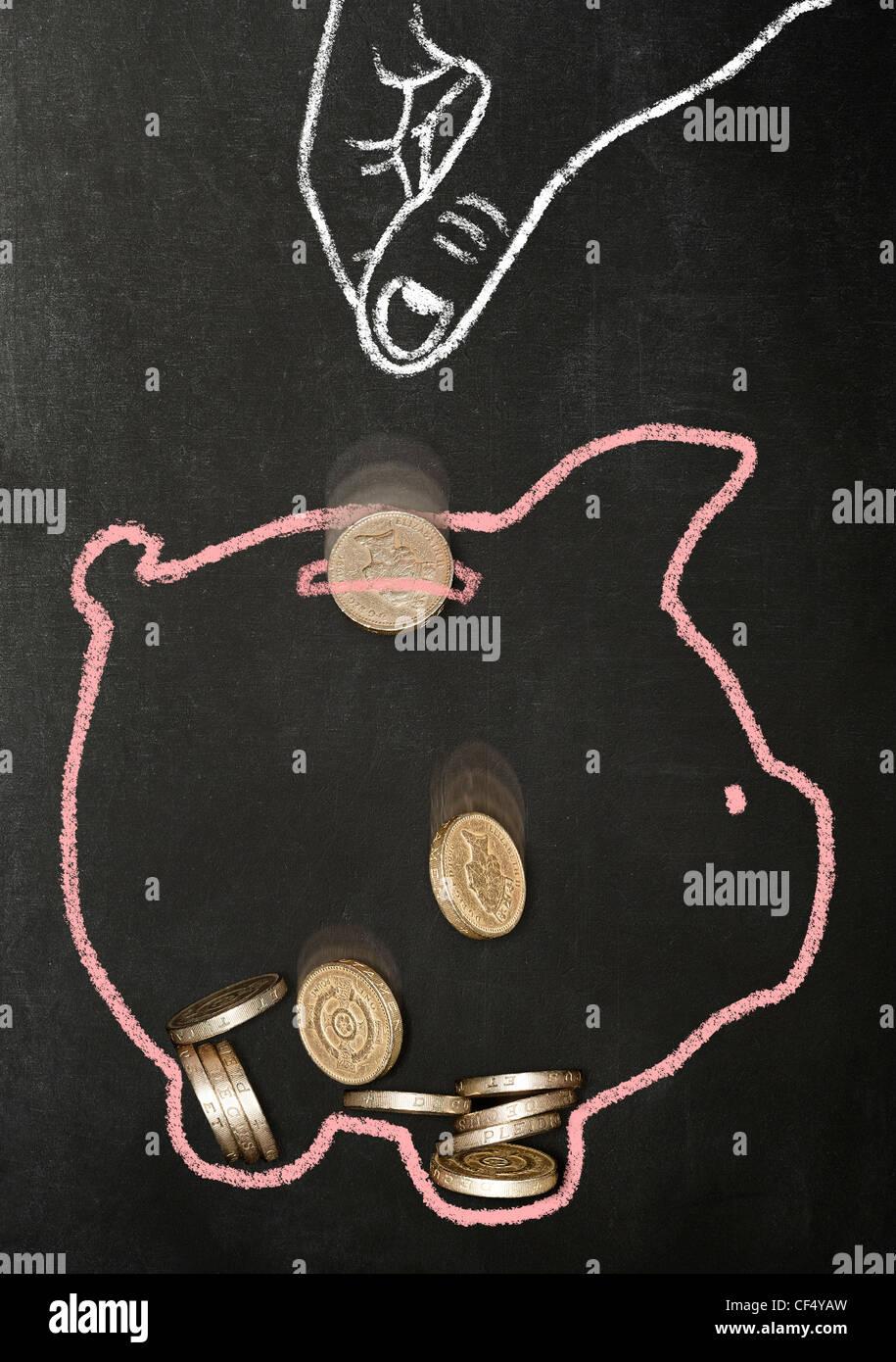 Kreide gezeichnete Hand fallenlassen echten Pfund Münzen in einem Chalk piggy Bank gezogen Stockfoto