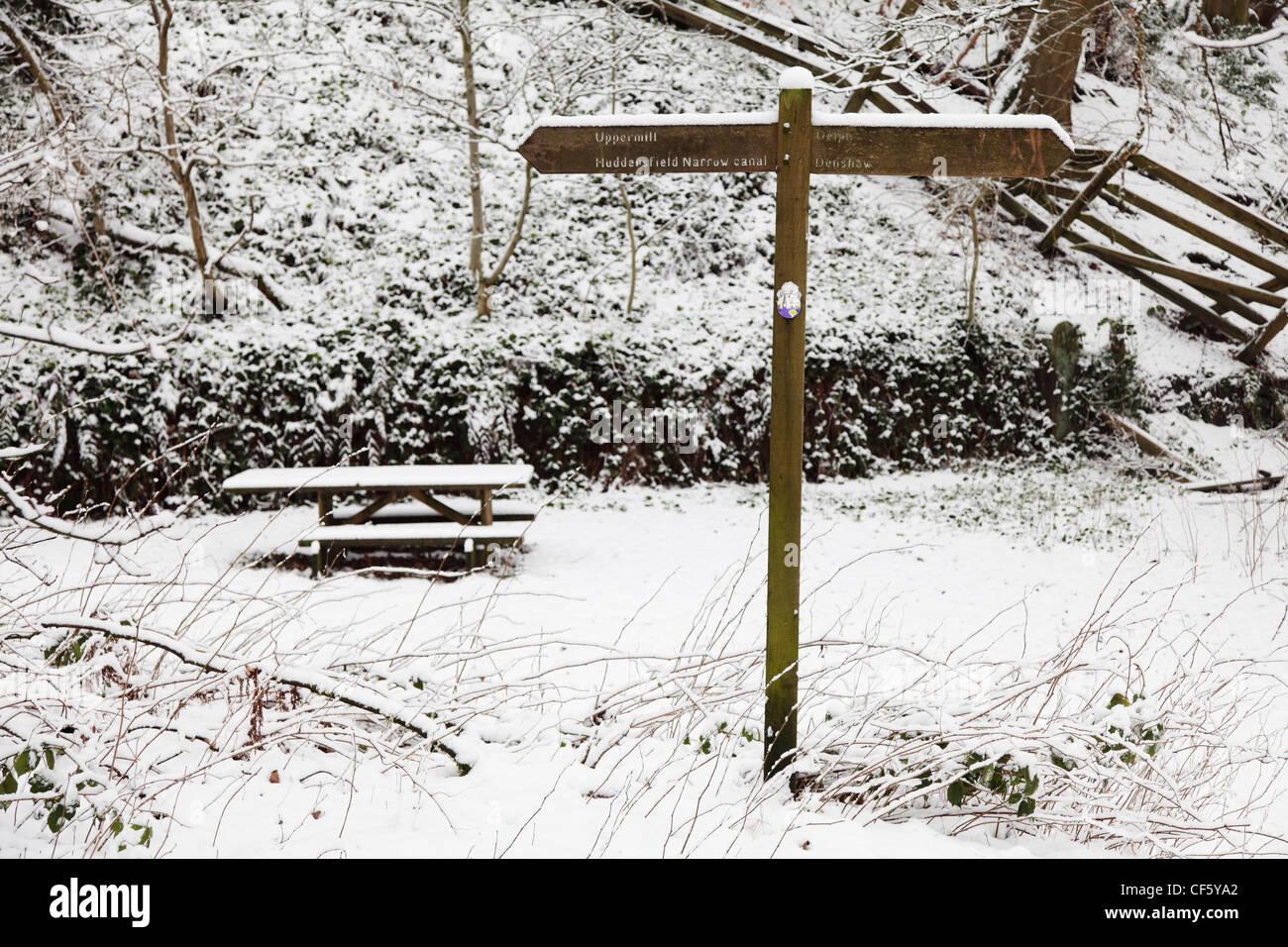 Wegweiser und Picknick-Bank mit Schnee bedeckt. Stockbild