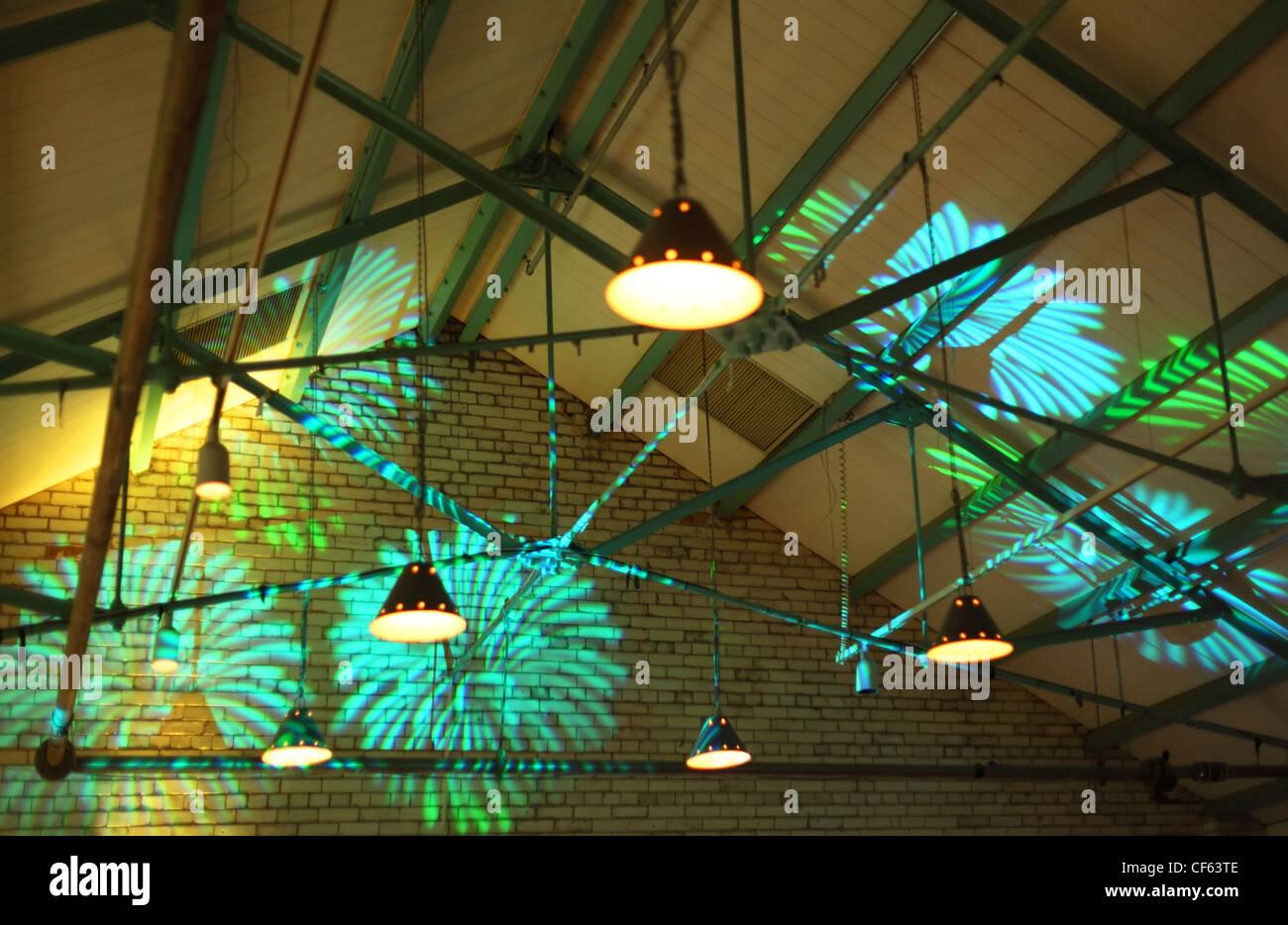 helle Beleuchtung. grüne und blaue abstrakte Formen auf Ziegelmauer Stockbild