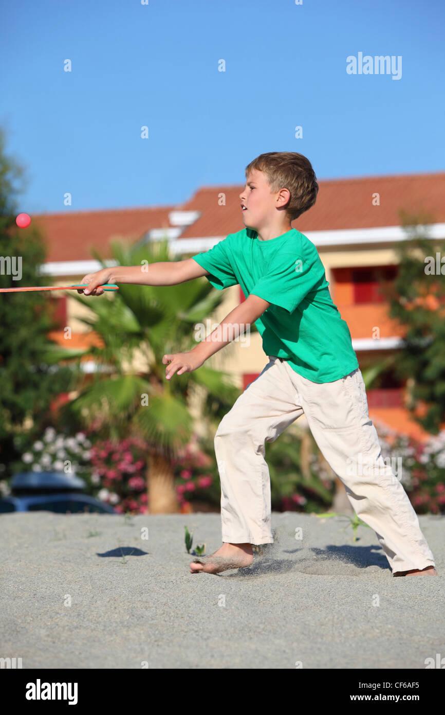 Junge fängt Ball Tennisschläger am Strand tagsüber in der Nähe von Hütten Stockbild