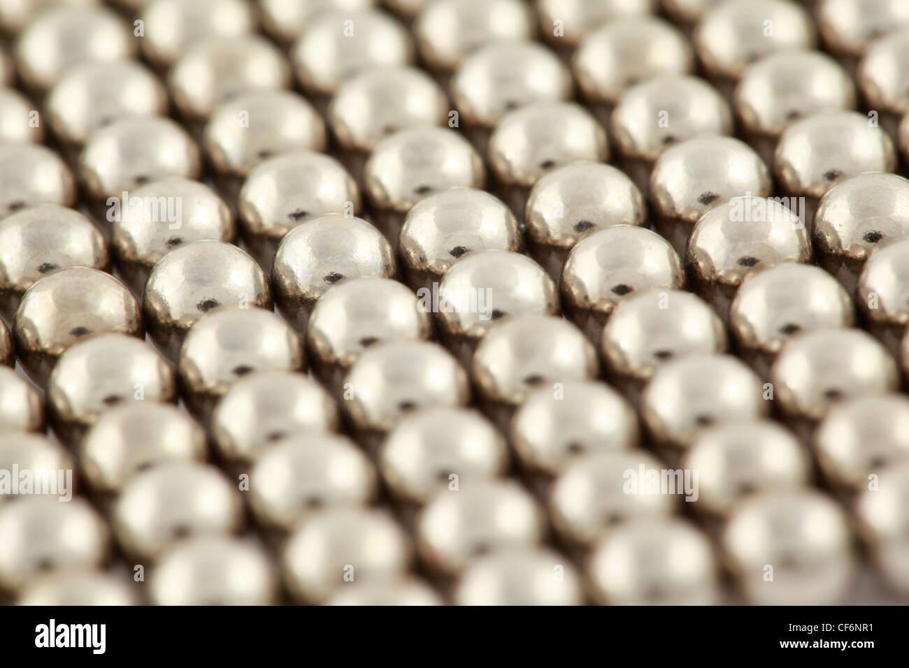 Silberne Perlen sind miteinander verflochten. Stockfoto