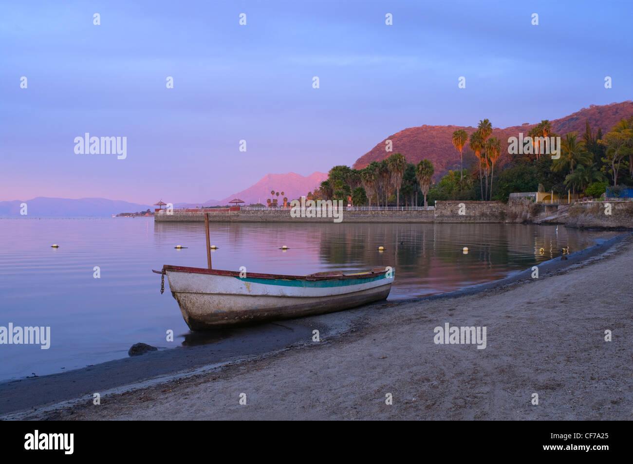 Chapala See in Jalisco Mexiko leuchtet im Morgengrauen mit Fischerboot am Strand und Pier und Berge in Ferne Stockbild