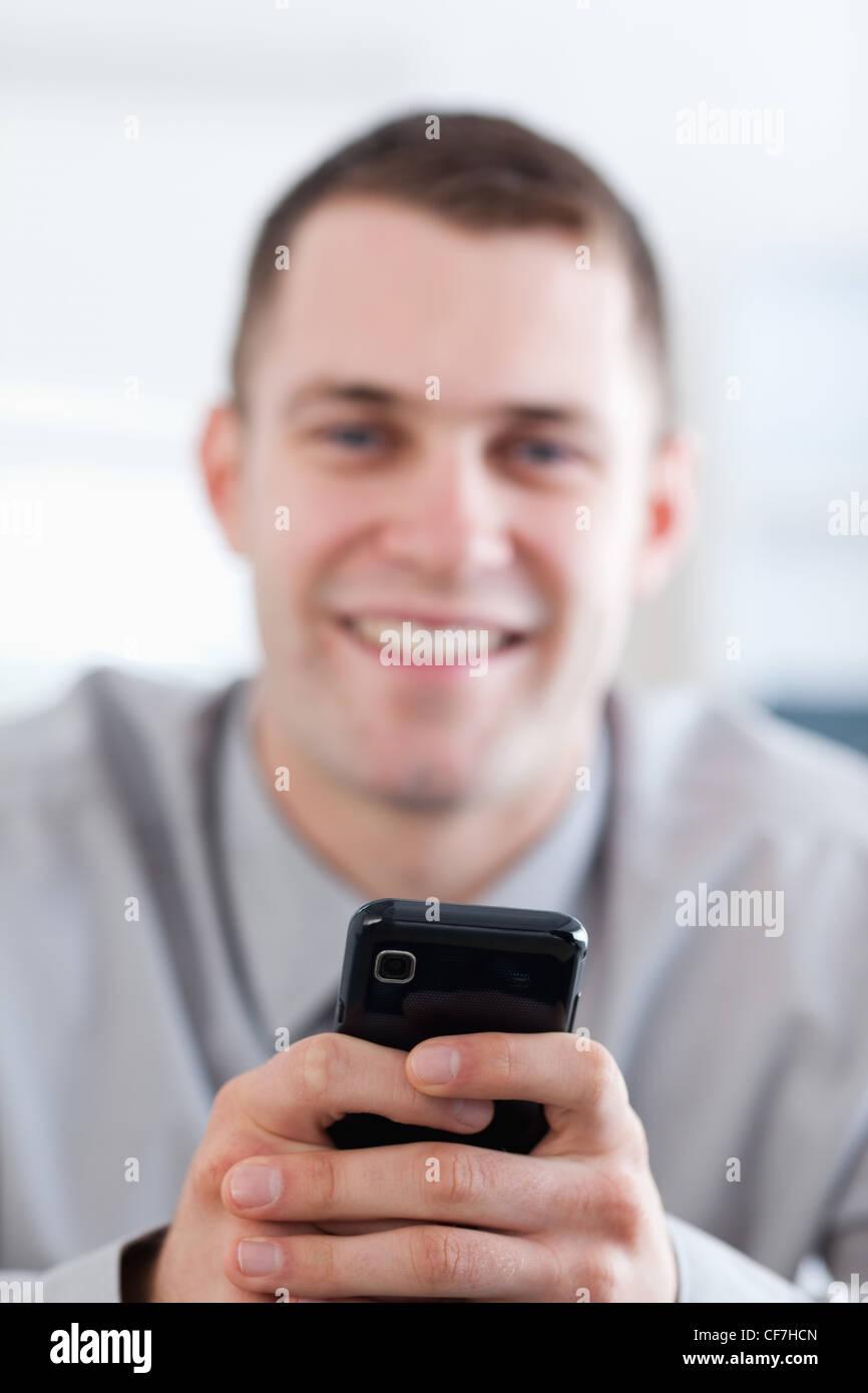 Nahaufnahme von Handy statt mit einem Lächeln Geschäftsmann Stockbild