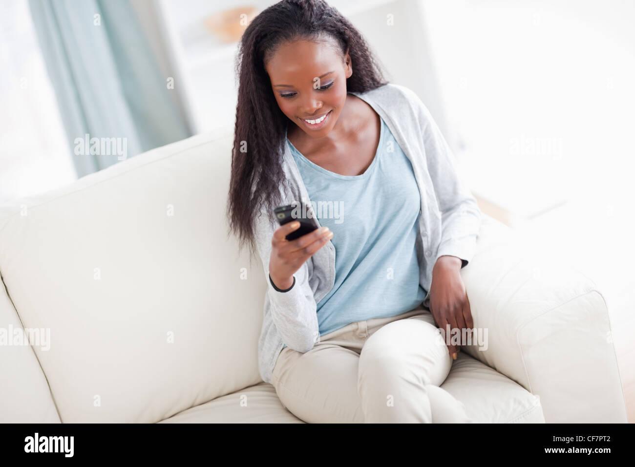 Frau auf Couch SMS lesen Stockbild