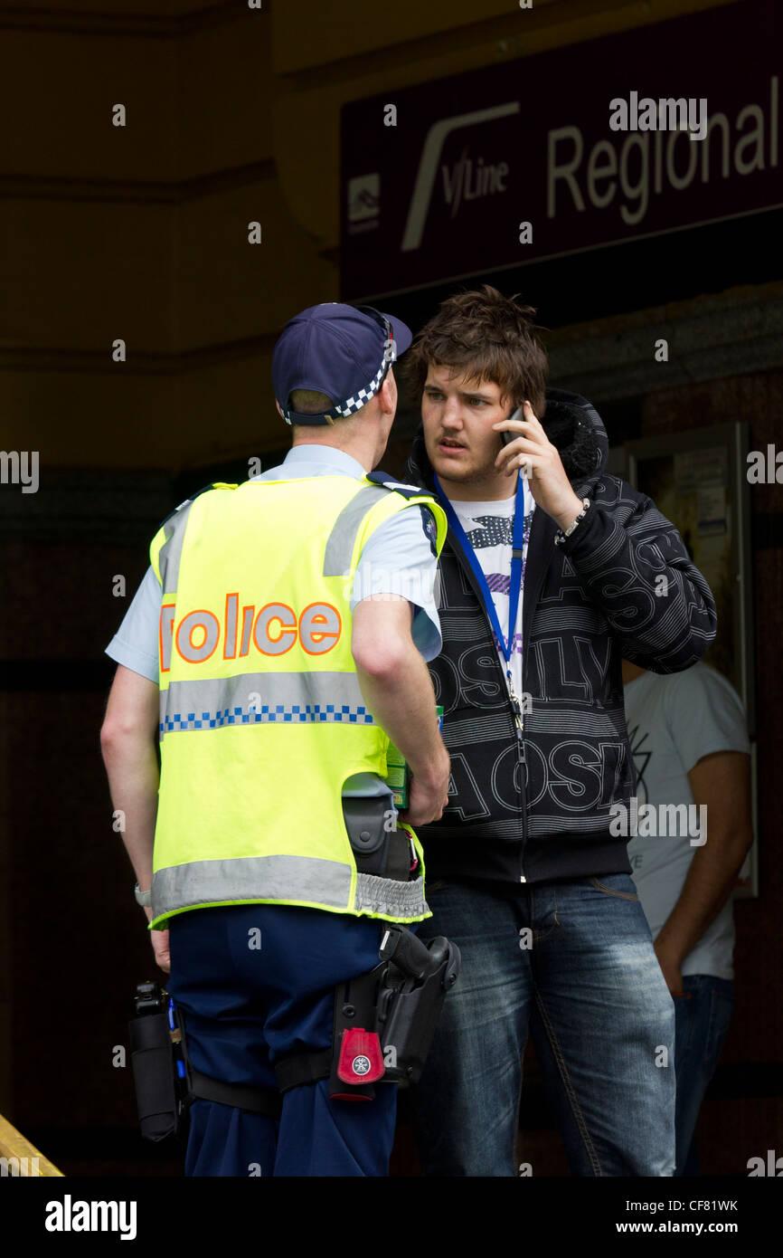 Polizist im Gespräch mit Jugendlichen auf Handy, Flinders Street Station, Melbourne, Australien Stockbild