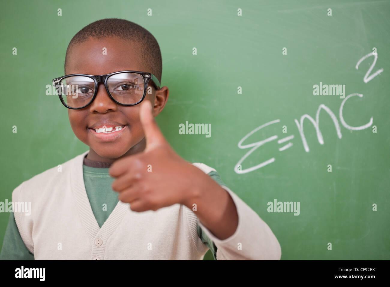 Schuljunge posiert mit der Masse – Energie-Äquivalenz Formel und der Daumen Stockfoto