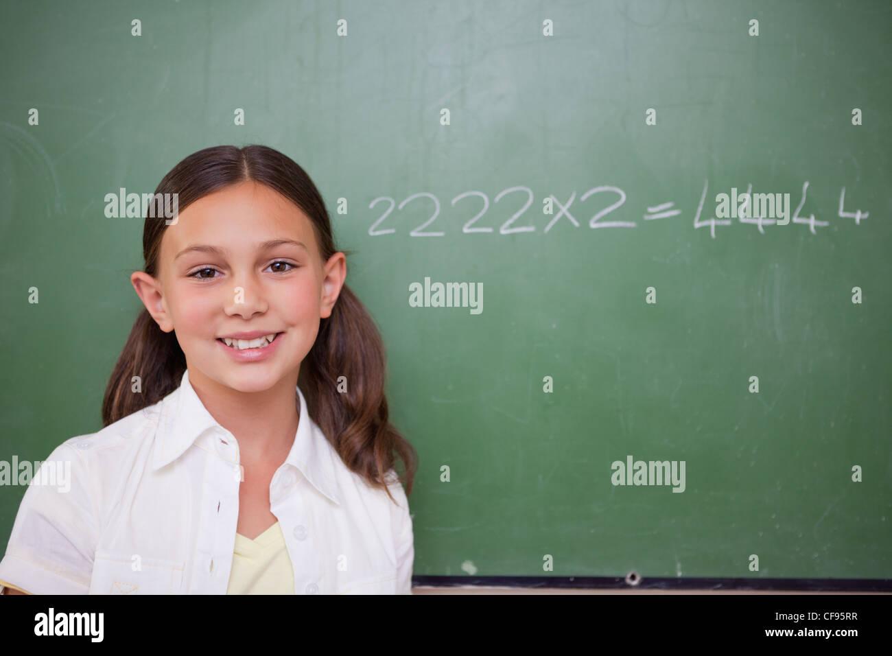 Schulmädchen posiert vor einer Tafel Stockbild