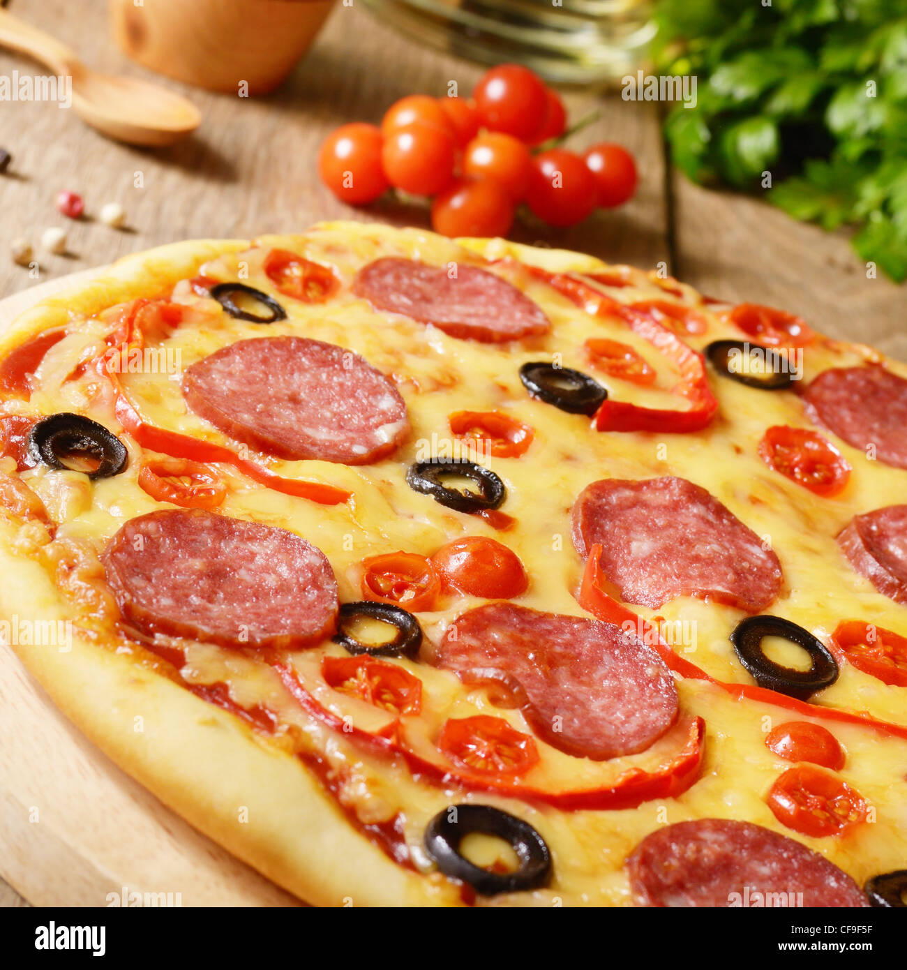 Peperoni-Pizza mit Kirsche und Paprika auf dem Küchentisch Stockfoto ...