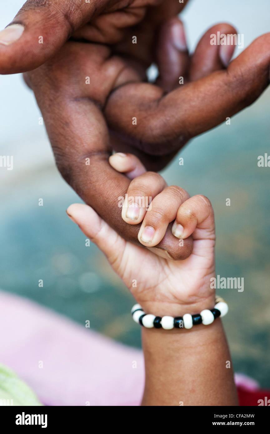 Indische mans Hand hielt seine Hand neue Babys geboren. Andhra Pradesh, Indien Stockbild