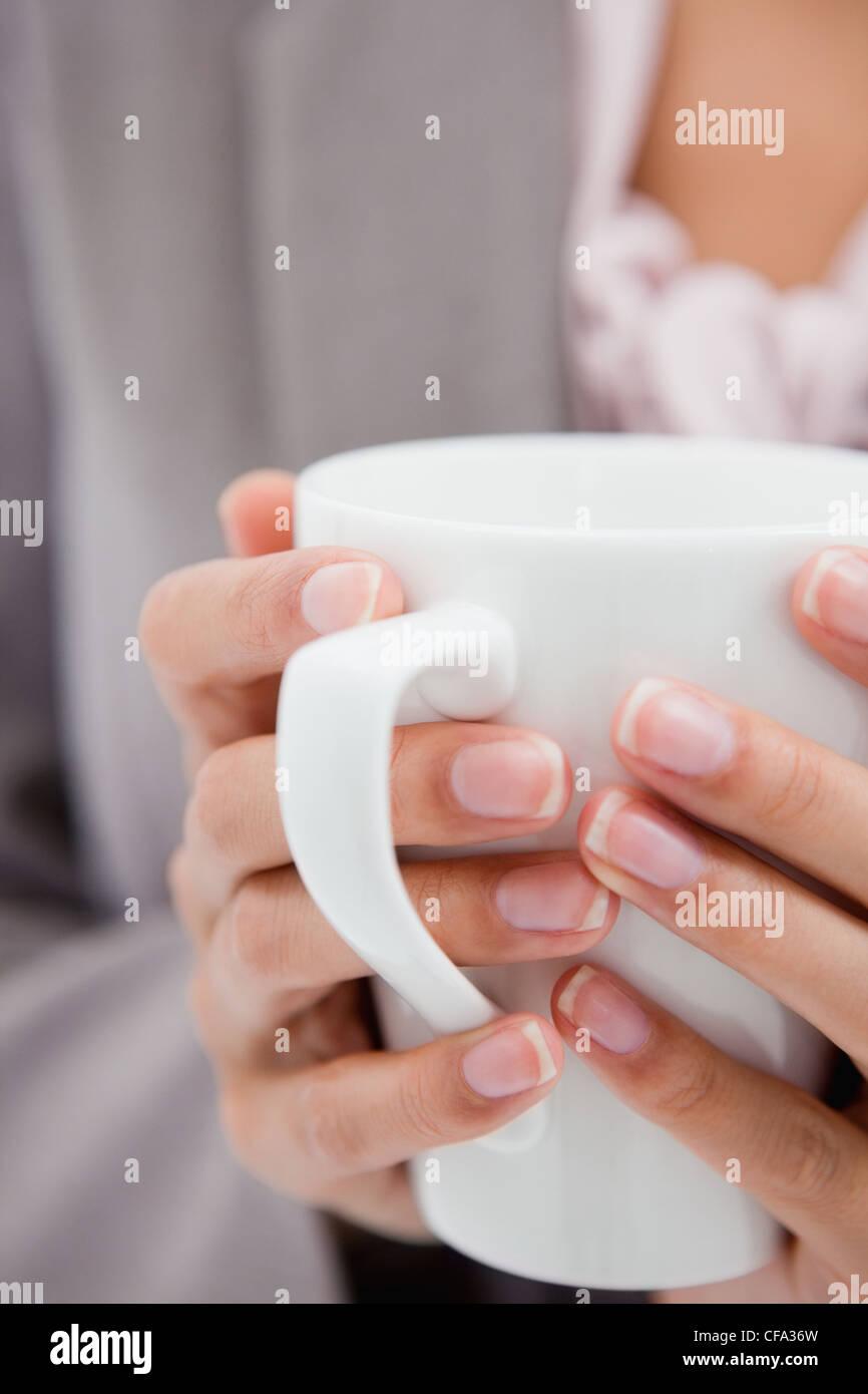 Tasse von weiblichen Händen gehalten Stockbild