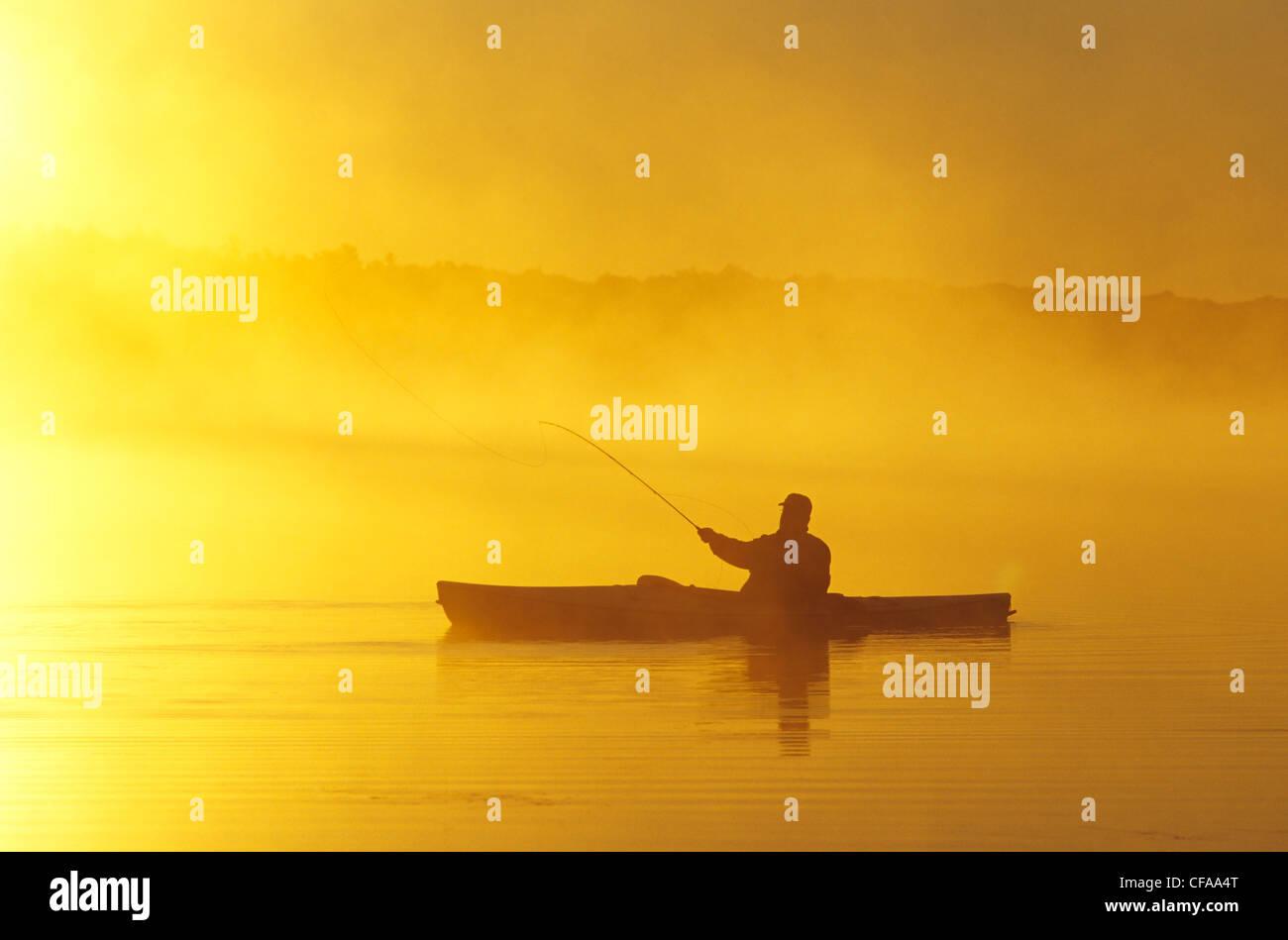 Mann mittleren Alters Fliegenfischen von Seekajak, Lake Muskoka, Ontario, Kanada. Stockbild
