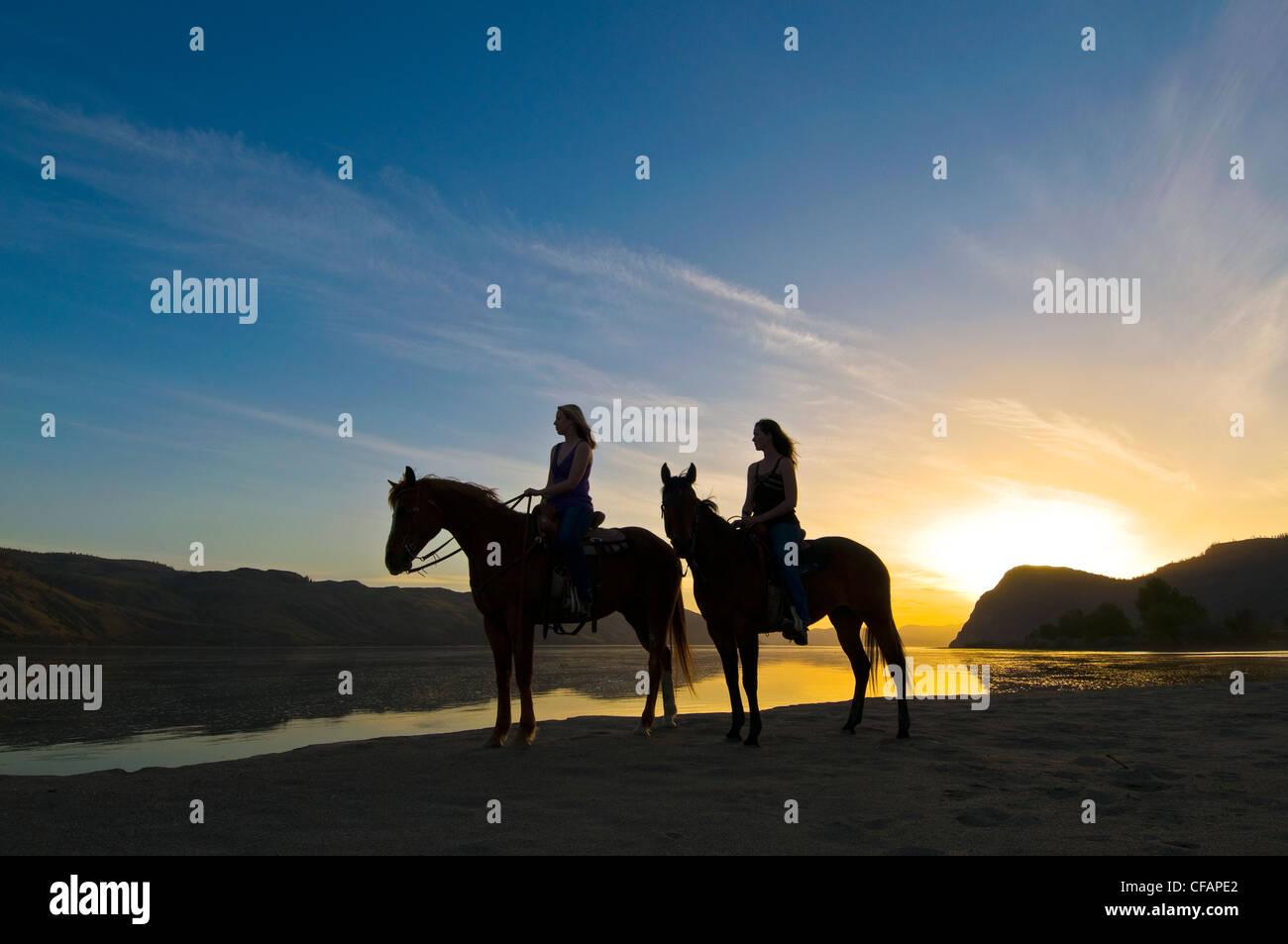 Zwei junge Frauen genießen atemberaubende Blick auf Pferden Sonnenuntergang Stockfoto
