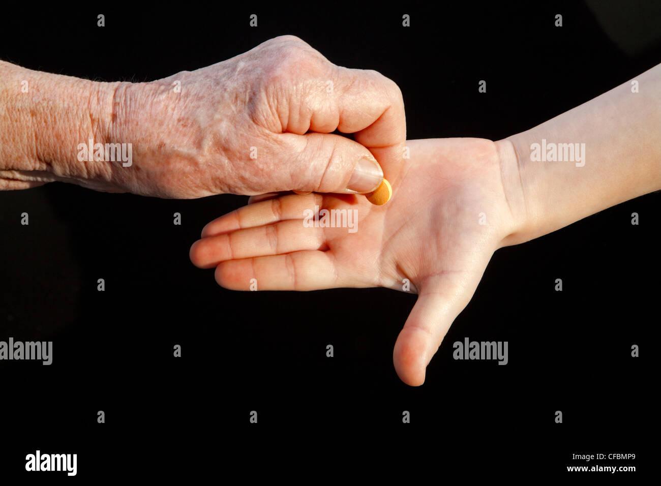 Hand der Großmutter und Enkel mit einer Pille Stockbild