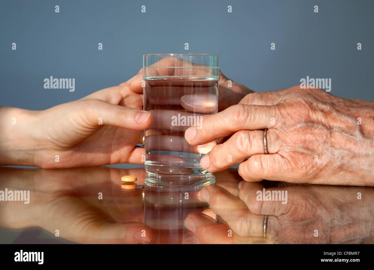 Hand der Großmutter und Frauen mit einer Pille Stockbild