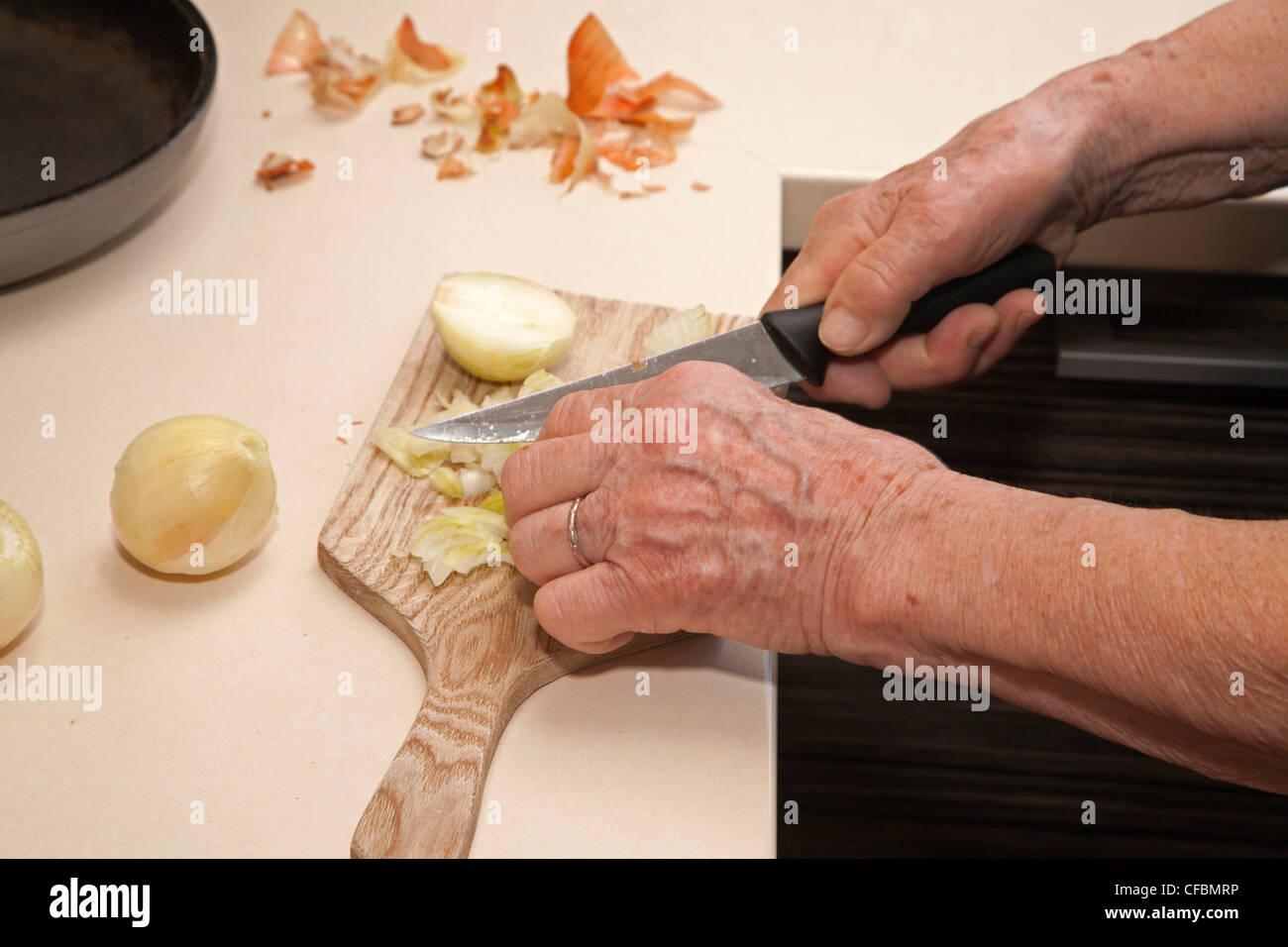 Händen der alte Frau beim Schneiden der Zwiebel Stockbild