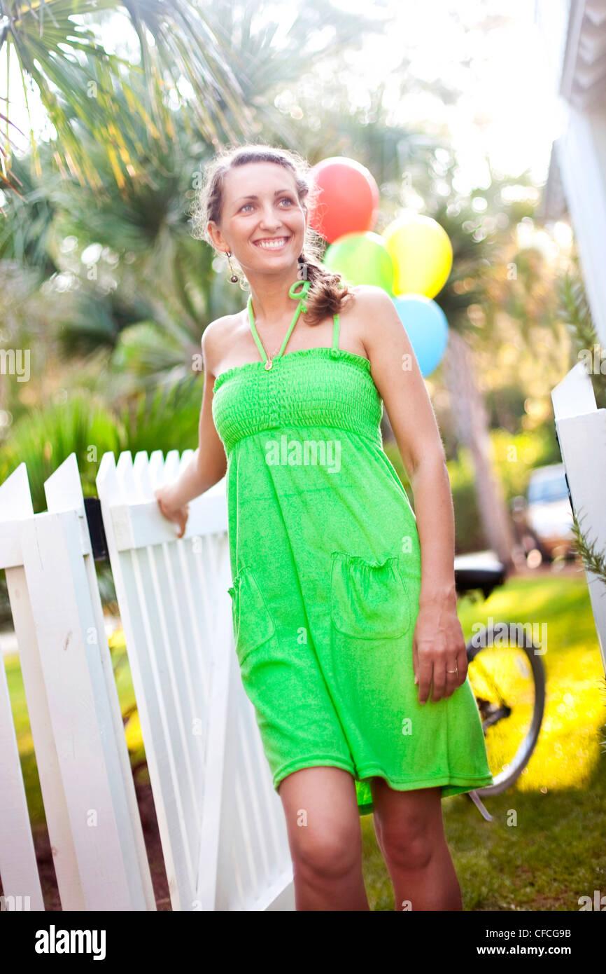 Eine junge Frau geht durch ein Lattenzaun in einem Strandhaus. Stockbild