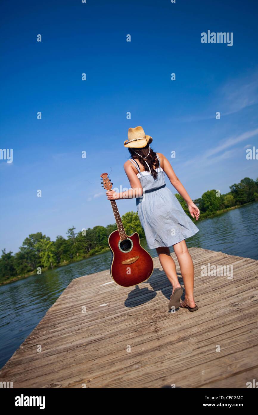 Ein Mädchen geht an einem Pier mit einer Gitarre in der hand. Stockbild