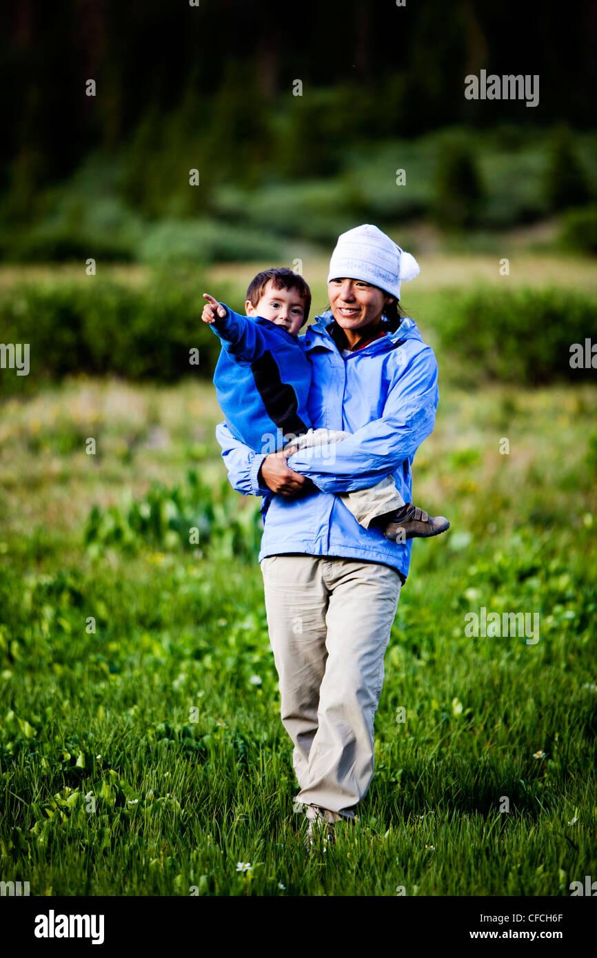 Eine Frau geht durch eine Wiese am Squaw Pass halten ihr 2 Jahre alten Sohn. Stockbild