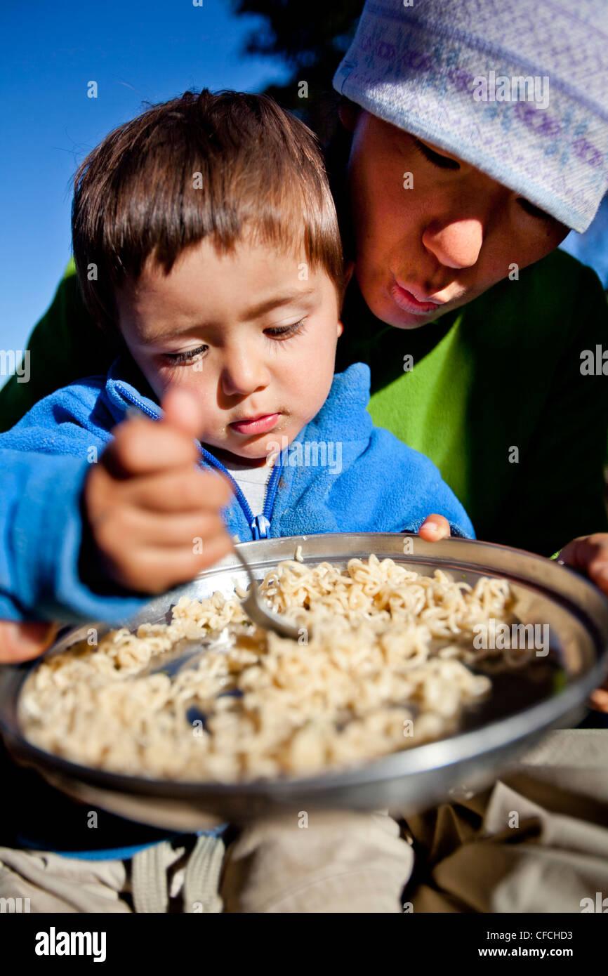 ein Junge sitzt auf seinem Schoß Mütter während sie Nudeln im Hinterland Essen. Sie sind am Squaw Pass lagerten. Stockfoto