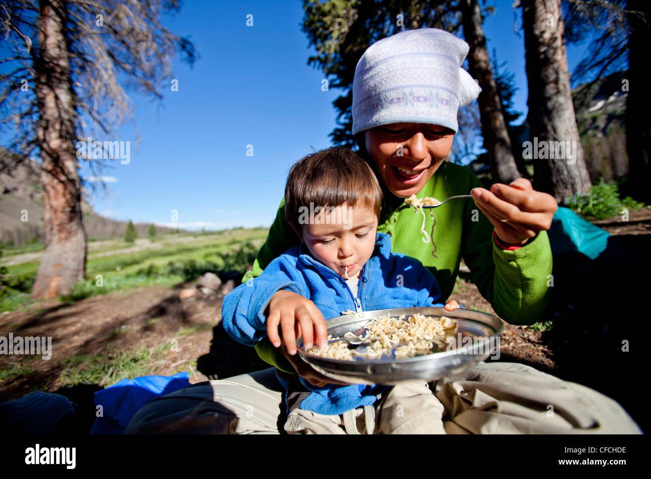 ein Junge sitzt auf seinem Schoß Mütter während sie Nudeln im Hinterland Essen. Sie sind am Squaw Stockbild