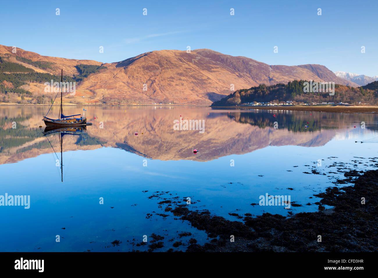 Malerische ruhige Loch Leven mit Segelboot und Reflexion von Glen Coe Dorf, Highlands, Schottland, Vereinigtes Königreich Stockbild