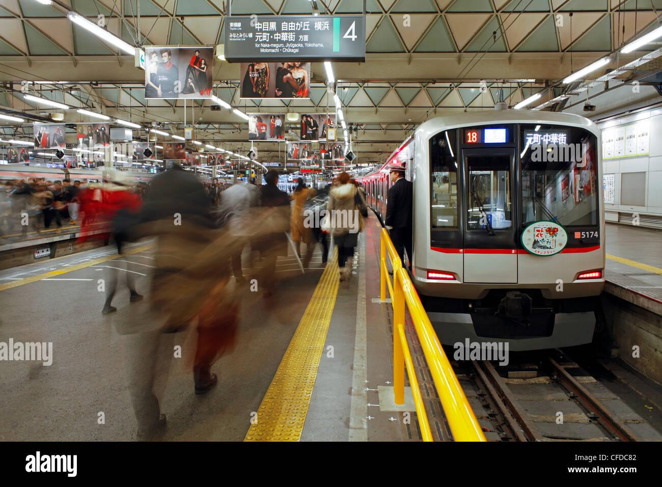 Pendler, die Bewegung durch Shibuya Station während der Hauptverkehrszeit, Stadtteil Shibuya, Tokyo, Japan, Stockbild
