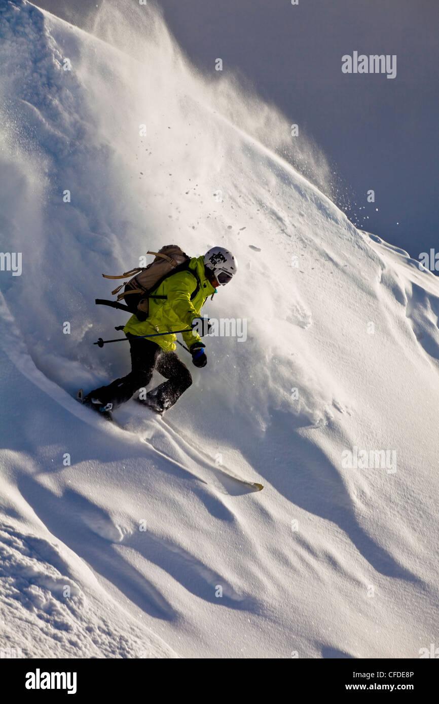 Ein junger männlicher Skifahrer Schrägstriche ein Pulver wiederum nur out of Bounds am Kicking Horse Resort, Stockbild