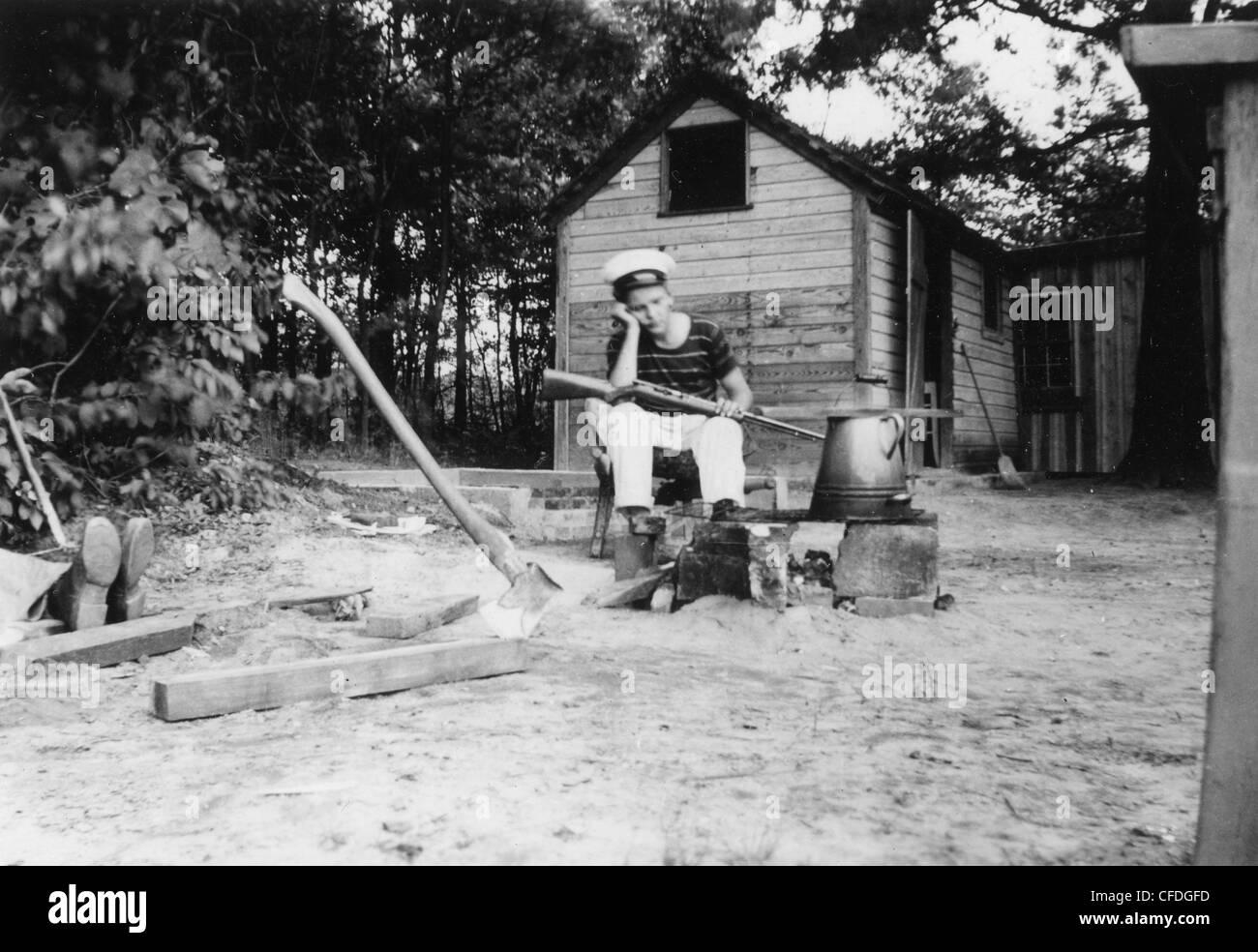 Junge sitzt mit Gewehr außerhalb Gehöft Haus Marine uniform Feuer Wasserkocher 1920s 1930s traumhafte Stockbild