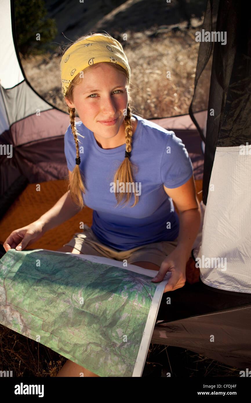 Frau sitzt in ihrem Zelt und eine Landkarte. Stockbild