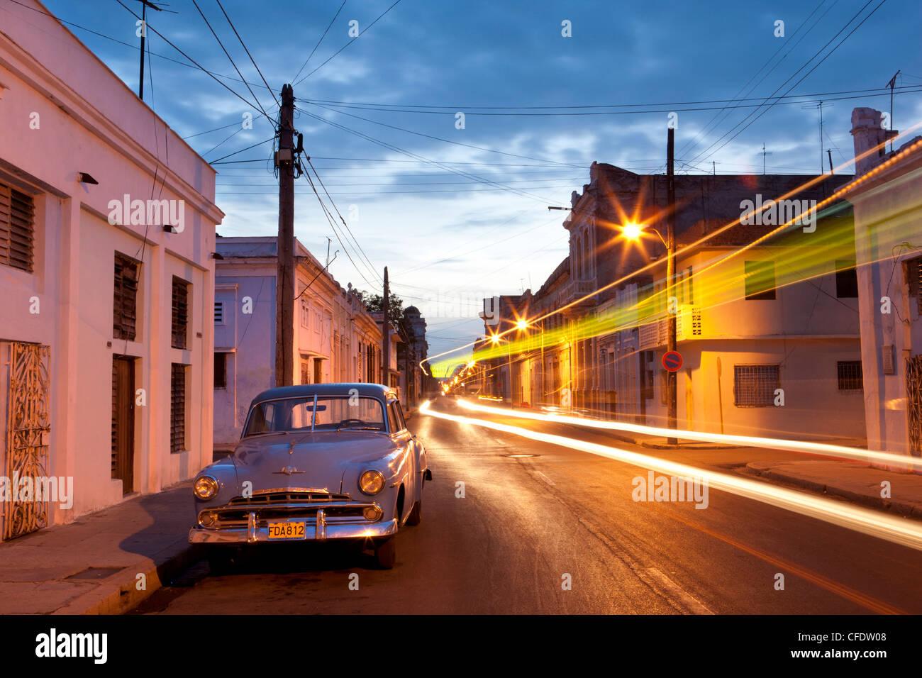 Straßenszene in der Nacht zeigt amerikanische Oldtimer und Lichtspuren der vorbeifahrenden Verkehr, Cienfuegos, Stockbild